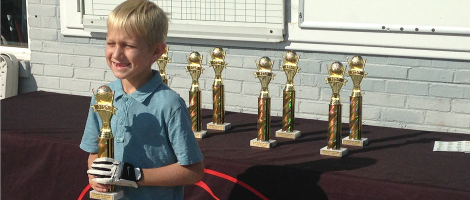 Zach Sullivan, winner of the 6 - 8 age group, smiles ear to ear with his first place trophy.